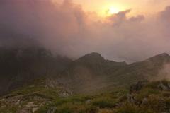 Fog rolling over ridge onto alpine meadow Carpathian mountains Fagaras massif 5K Stock Footage