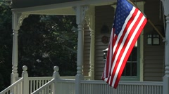 American Flag outside house in a small town, morning Stock Footage