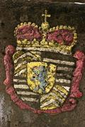 colored heraldic figure on an historical boundary stone - stock photo