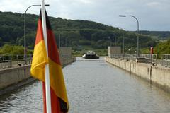 german national flag with sluice watergate and incoming boat on main-danube-c - stock photo