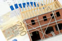 Stock Photo of bare brickwork model with banknotes