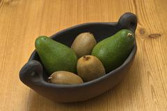 Avocados and kiwi fruits in an archaic clay bowl Stock Photos