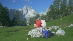 AERIAL: Hikers sitting on rock adimirng the view Stock Footage