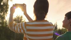 Two kids taking a photo with mobile phone in nature in the evening Stock Footage