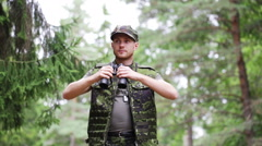 Young soldier or hunter with binocular in forest Stock Footage