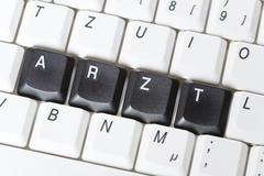 """arzt"" (doctor) spelled out in black keys on a keyboard - stock photo"