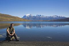 tourist at the lake laguna azul, torres del paine mountains, national park to - stock photo