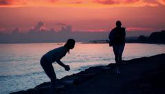 Successful couple of joggers by the see during sunset HD Stock Footage