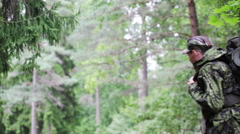 Young soldier with backpack in forest Stock Footage
