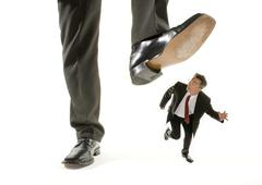 Giant foot stepping on a kneeling businessman running away Stock Photos