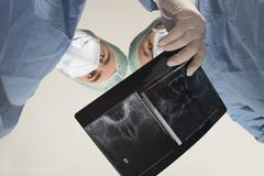 Two doctors examining an x-ray image (radiograph) Stock Photos