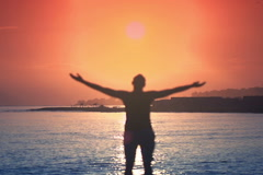 Prayer rising arms to the sky by the sea NTSC Stock Footage