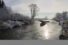 winterly landscape with hoar-frost, stream and blue sky in the morning sun - stock photo