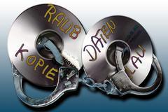 Handuffs and cd/dvd: symbolic for data theft crime Kuvituskuvat