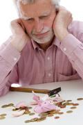 Stock Photo of retiree robs the piggy bank