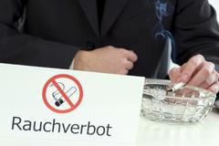 Smoking in spite of ban of smoking Stock Photos