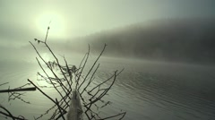 Mountain lake surrounded by morning fog at sunrise - stock footage