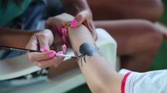 Woman paints a spider on the hand of a boy, Antalya, Turkey 2 Stock Footage