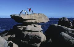 climber erecting a tent on roche tremblante (shaking rock) near ploumanach, b - stock photo