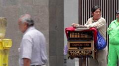 MEDIUM SHOT-HANDHELD SHOT. Organ grinder, playing the organ in the street. Stock Footage