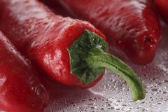 Stock Photo of fresh red capsicums covered in water droplets