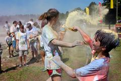 Family throws colored corn starch at bubble palooza event Stock Photos