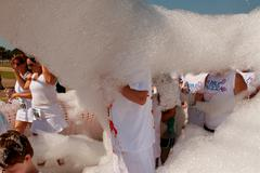 People walk through cloud of foam at bubble palooza event Stock Photos