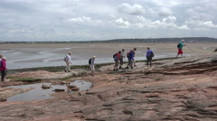 Active senior walkers walk to hilbre island, wirral, england, uk Stock Footage