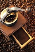 Stock Photo of coffee grinder atop a bed of coffee beans