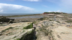 pan of sandstone rock of hilbre island with view to irish sea, wirral, englan - stock footage