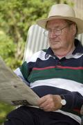 Stock Photo of a relaxing senior citizen sitting in the garden reading a newspaper