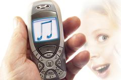hand holding a mobile phone with music-note display: symbol for ringtones - stock photo