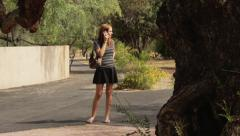 Exasperated Cute Young Woman on Phone Looking for Friend in Park Stock Footage