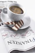 cup of espresso sitting on top of newspaper, financial section - stock photo