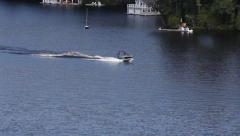 COTTAGE: WATERSKI BOAT PULLS WATERSKIER 2 Stock Footage