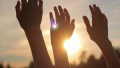 Stock Video Footage of Close-up of raised hands in the sky against the sun, freedom, camera movement