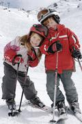 two children skiing in the mountains - stock photo