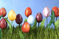 Colourful tulip bed made of easter eggs on artificial lawn Stock Photos