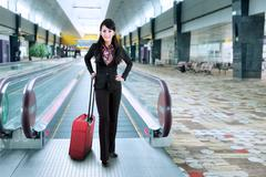 businesswoman standing on escalator - stock photo