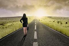 businesswoman standing on the highway road - stock photo