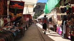 Peru Pisac market shoppers walk past goods on display 4 Stock Footage