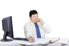 Fat businessman working while eating Stock Photos