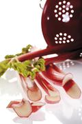 Rhubarb (rheum rhabarbarum) with red kitchen sieve Stock Photos