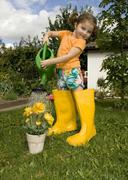 Girl watering her yellow flowers wearing yellow rubber boots Stock Photos
