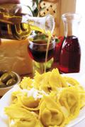 italian ambiance: drizzling olive oil over an agnolotti dish with parmesan, r - stock photo