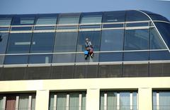 Abseiled window cleaner cleaning glass roof Stock Photos