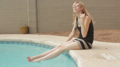 Cute Leggy Tattoo Blonde Girl in Glasses Sitting by Pool with Feet in Water Wide Stock Footage
