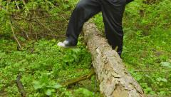 A man walking through the woods crosses a fallen tree Stock Footage