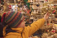 A boy 7 year old is watching christmas decoration at the christmas market aug Stock Photos
