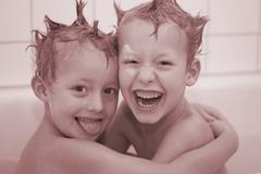 Two little boys 5 and 7 year old loughing in the bath tub Stock Photos